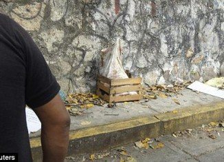 A police officer in Acapulco stands next to the sack containing five severed heads which has been placed in a small wooden crate