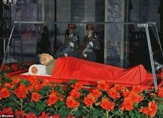 North Korean state television showed still images of the Kim Jong-Il body in the open coffin, surrounded by wreaths and covered with a red blanket