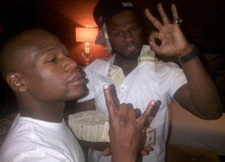 50 Cent has showed off his money literally in a series of vulgar poses on his Twitter page