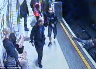 A crazed commuter launched an apparently random attack on a young woman, pushing her on to the tracks of the London Underground