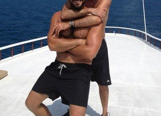 George Michael is seen smiling widely while hugging Fadi Fawaz, who is also beaming with delight