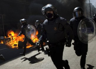 Spanish riot police have clashed with protesters in Barcelona on the day of a general strike called in protest at the government's labor market reforms