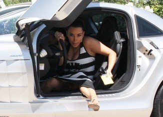 Kim Kardashian was spotted yesterday struggling to make a graceful exit from Kanye West's silver sports car