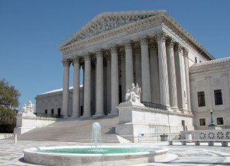 Part of a tough Arizona immigration law giving police powers to check the immigration status of people stopped and arrested has been upheld by the US Supreme Court