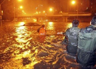 Beijing has been hit by the heaviest rainfall in 60 years and has left 10 people dead and stranded thousands at the main airport