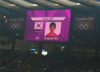 London Olympic organizers have apologized to the North Korean women's football team after their images were shown on a screen beside a South Korean flag