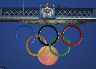 Reuters photographer Luke MacGregor's perfectly timed snap captured the full moon forming a sixth ring in the Olympic display on London's Tower Bridge