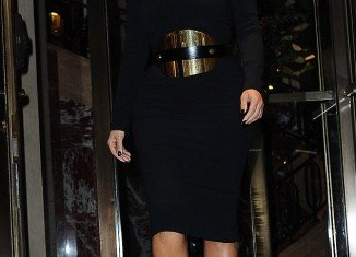 Kim Kardashian looked rather striking despite the plain black high-neck dress thanks to the efforts of her giant metal belt around her waist