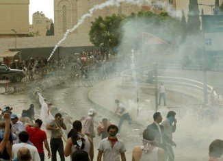 Clashes have erupted outside government offices in Beirut after thousands attended the funeral of Wissam al-Hassan