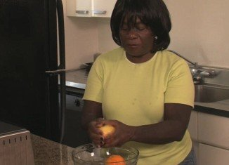 Alfreta shows on Neat Freaks how she pours a cap-full of bleach into a bowl mixed with water to clean her fruit from its contaminated insecticide