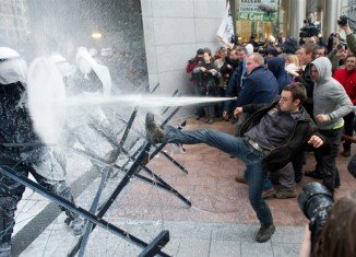 Angry farmers protesting at falling dairy prices in the EU have sprayed fresh milk at the European Parliament and riot police in Brussels