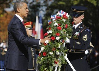 President Barack Obama laid a wreath of flowers at Arlington National Cemetery on Sunday in a traditional gesture as Americans marked three days of Veterans Day commemorations