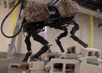 Four-legged robot BigDog now sports an arm powerful enough to lift and throw breeze blocks