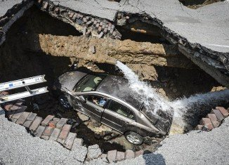 Ohio driver Pamela Knox had to be rescued from her vehicle after it plunged into a 10-feet deep sinkhole that suddenly appeared in the road