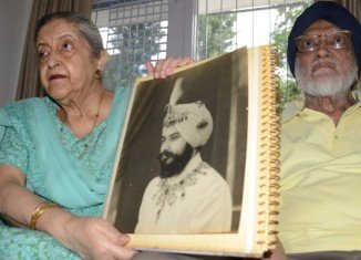 Amrit Kaur, the daughter of late Maharaja Harinder Singh Brar of Faridkot, poses with a portrait of her father