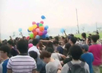 People arrived with BB guns and knives on sticks for a race to grab LG G2 smartphone vouchers hanging from helium balloons