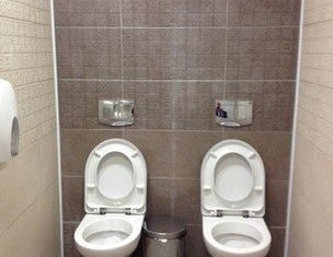 Twin toilets in a cubicle at Sochi Olympics venue