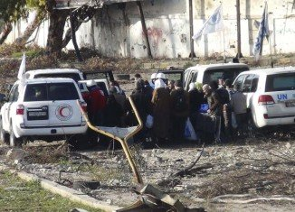 A UN aid convoy bringing supplies into the besieged district of the central Syrian city of Homs has come under fire, leaving at least one person hurt